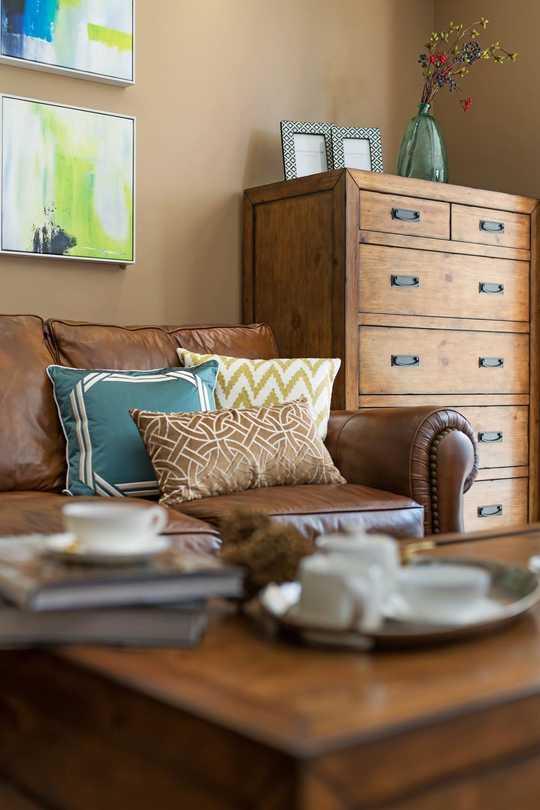 深棕色的铆钉皮沙发搭配颜色鲜艳抱枕